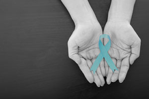 Hands holding teal ribbon